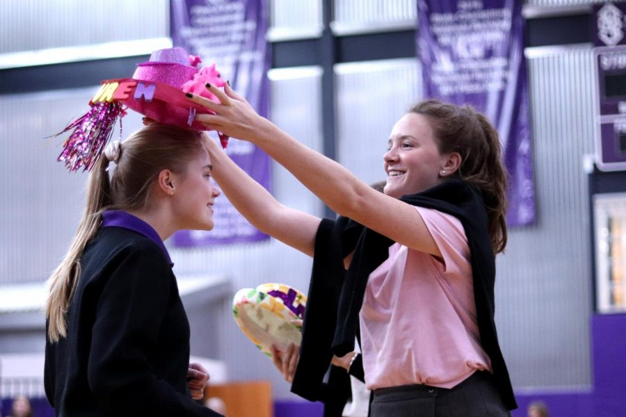 Senior Brooke McKee arranges a gleaming pink top hat on freshman Lauren Smith.