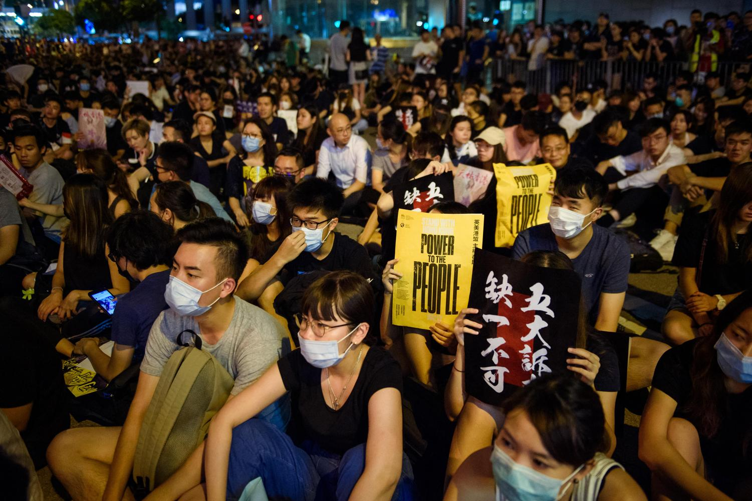 During a protest rally in front of the Chater Garden in the Central District, participants hold up signs with the inscription