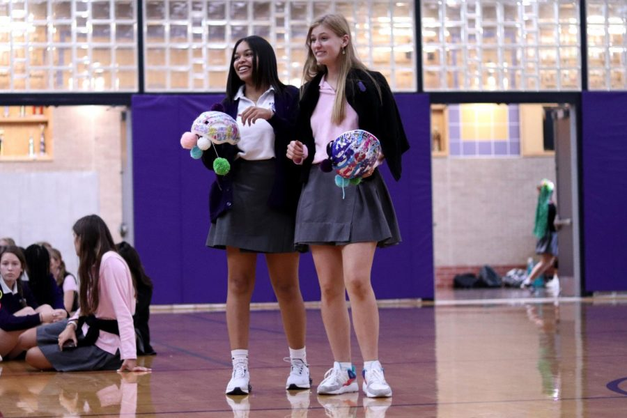 Holding embellished bike helmets, seniors Avanni Martin and Elyse Makar prepare to present their maison freshmen Sophie Gromowsky and Zahra Parsons with their beanies.