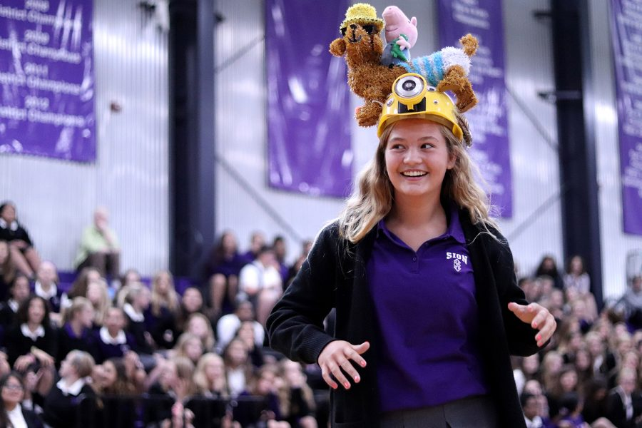 Walking away after recieving her beanie, freshman Brynna Fitzgerald shows off to her classmates in the gym during the beanie ceremony on Aug. 22.