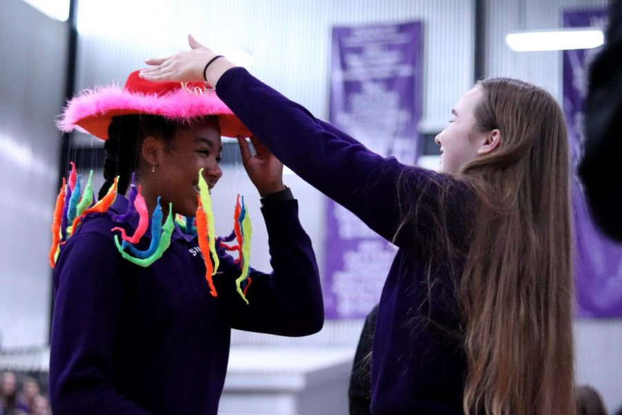 Senior Peyton Wade positions the fur-lined beanie complete with squiggly worms dangling on freshman Kori Franklin's head.