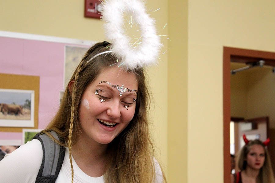 dressed in white clothing with a furry halo for Spirit Week theme Devils and Angels, Senior Maddy Anstoetter talks with classmates before her second-hour class Sept 11.