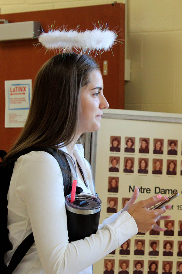 Senior+Caroline+Boessen+texts+on+her+phone+before+school+Sept.+11.+For+the+third+day+of+Spirit+Week%2C+students+participated+in+the+Devils+and+Angels+theme.+