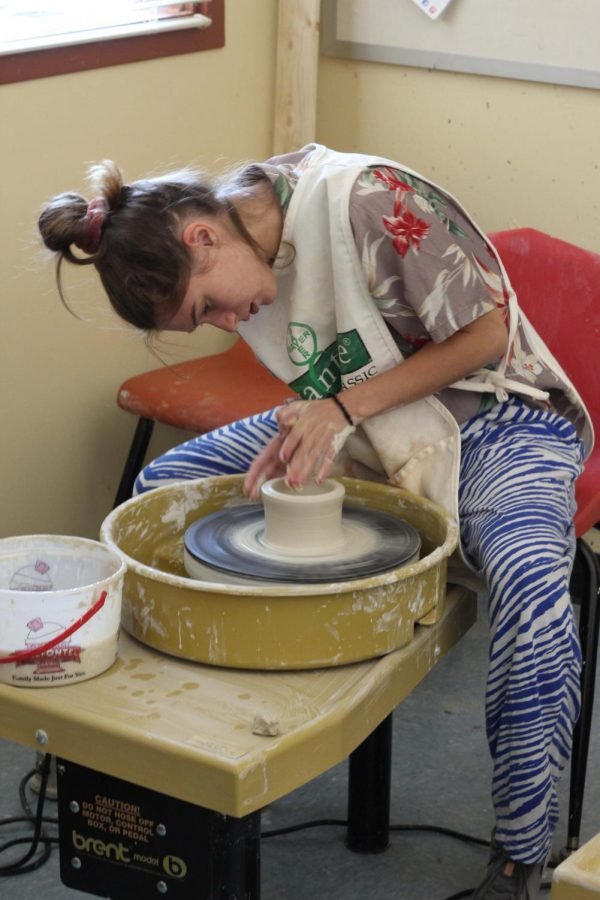 Senior Lauren Mead works on her project in her ceramics class Sept. 9. Underneath her apron, Mead is dressed in a combination of various patterns for Pattern Day, the first day of Spirit Week.