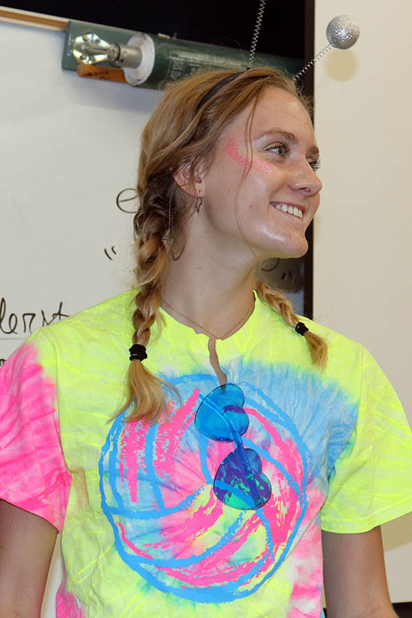 Dressed+in+yellow%2C+pink+and+blue+neon+colors%2C+senior+Lily+Henkle+converses+with+peers+before+class+Sept.+10.+Students+dressed+in+Area+51-themed+costumes+for+the+second+day+of+Spirit+Week.+