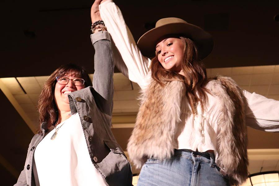 Senior Peyton Wiewel and her mom Sabrina Wiewel hip bump during the fashion show. Sept. 15