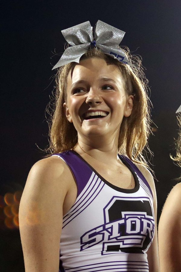 Senior Brooke McKee looks over at the students cheering for her from the stands. This was Mckee's last year performing with cheer at the Rockhurst football game during halftime Sept. 13.