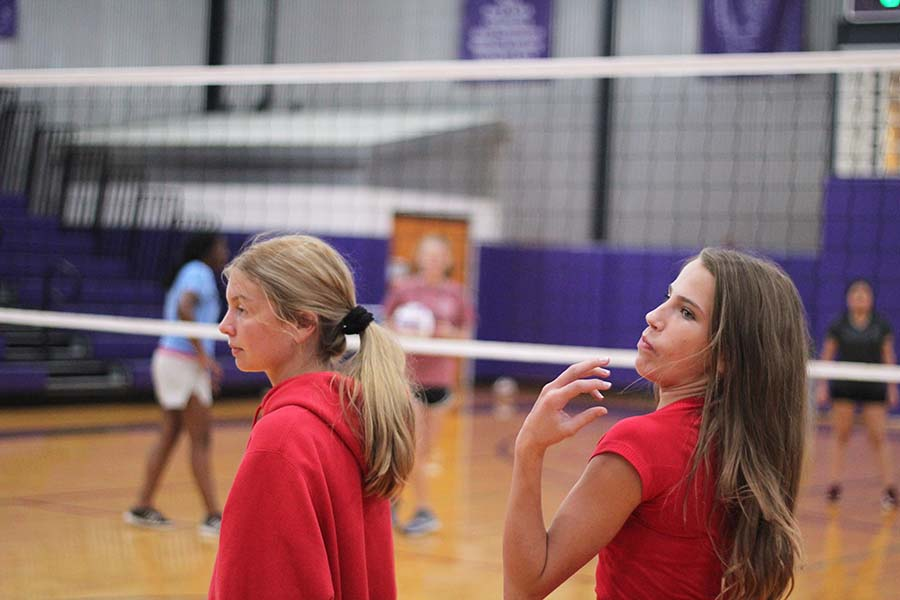 Freshmen+Emily+Dierks+and+Mallory+Vance+wait+to+get+on+the+court+to+play+a+volleyball+game+during+physical+education+Wednesday+afternoon.+Both+were+dressed+in+red+for+Devils+and+Angels+Spirit+Week+day+Sept.+11.