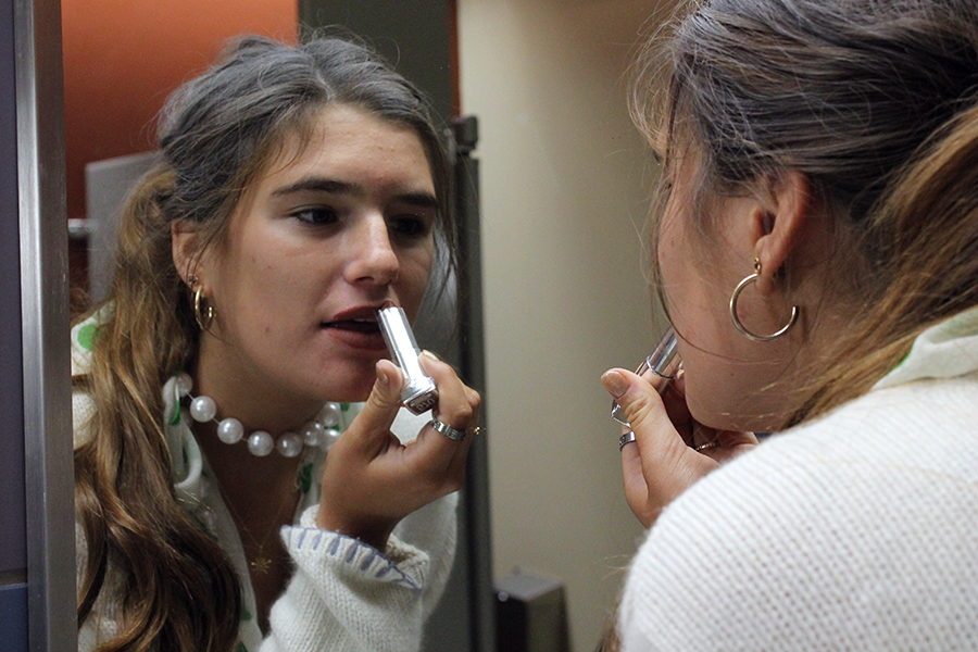In between classes, Senior Reilly Jackoboice applies lipstick in the South C bathroom Sept. 11. For day four of spirit week, seniors dressed as senior citizens.