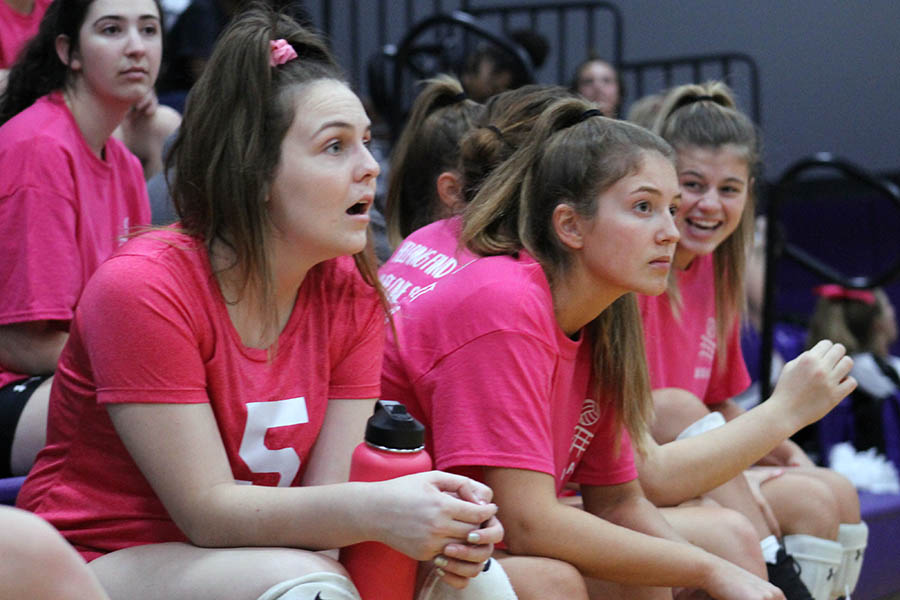 Seniors Abby Gahagan and Katie Fitzgerald observe the game from the bench at the annual Dig Pink volleyball game Oct. 3. The annual game in support of breast cancer awareness raised $1,300 for the Susan G. Komen foundation.