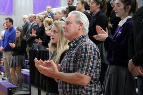 Senior Madi Brown and her father Kevin Brown join in the school song at the Father-Daughter Mass Nov. 1.