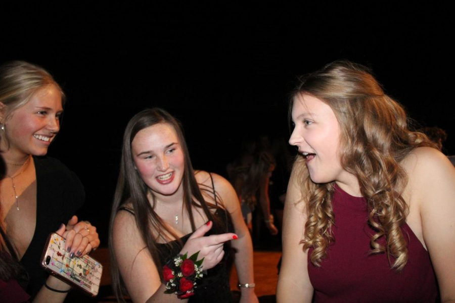 Juniors Sharon Kramschuster, Mason Lewis and Haley Langle share a laugh at Winter Formal on Dec 7.