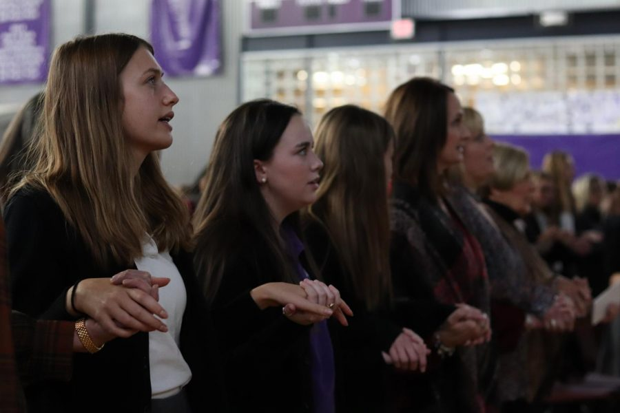Seniors Elizabeth Finn and Allie Dierks holds during the Mass service Nov. 5 at the annual Mother-Daughter-Grandmother Mass. Finn and Dierks both offered presentations during the Mass alongside their mothers.