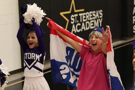 Senior Brie Bowes and freshman Emily Dierks hype up the crowd before the varsity basketball game at St. Teresa