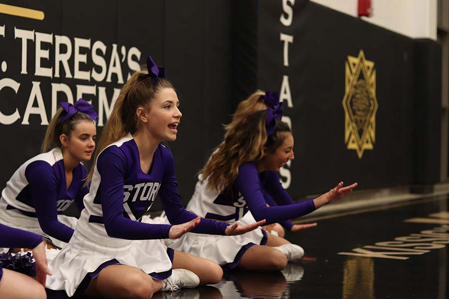 Senior Rachel McRae and juniors Bella Aquino and Sophia Allen perform a cheer during the varsity basketball game against St. Teresa's Academy at STA Dec. 6.