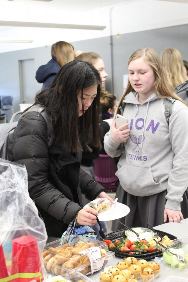 Junior Lia Concannon joined with junior Katherine Lillis at the buffet for fruit at the Spanish club breakfast Jan. 22.