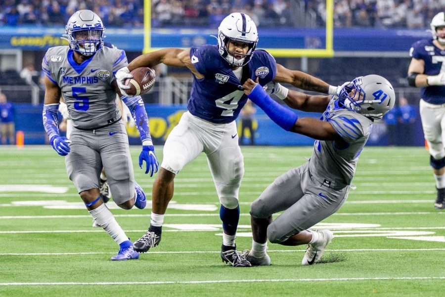Penn State running back Journey Brown stiff arms Memphis defensive back Sanchez Blake Jr. as he goes 32 yards for a touchdown during the first quarter of the 84th Cotton Bowl in AT&T Stadium,