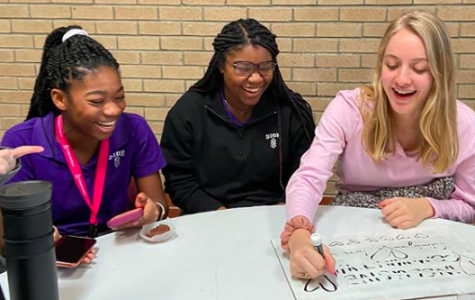 As the kick off to Catholic Schools Week, seniors and freshmen met up for a Peer Ministry meeting during lunch and study hall Jan. 27. Freshman Makaila Traylor, senior Maya Scott and senior Elizabeth Crabtree write on the white board their answers to the discussion question