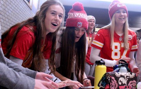 Seniors Felicia Knox, Reilly Jackoboice and Logan Dixon join students in cheering 'Go Chiefs!' during the Red Friday tailgate Jan. 31. During all lunch periods, students were invited to the Grande Salle for the tailgate in support of the Kansas City Chiefs' upcoming Super Bowl LIV game. The tailgate consisted of a concession stand, music and games.