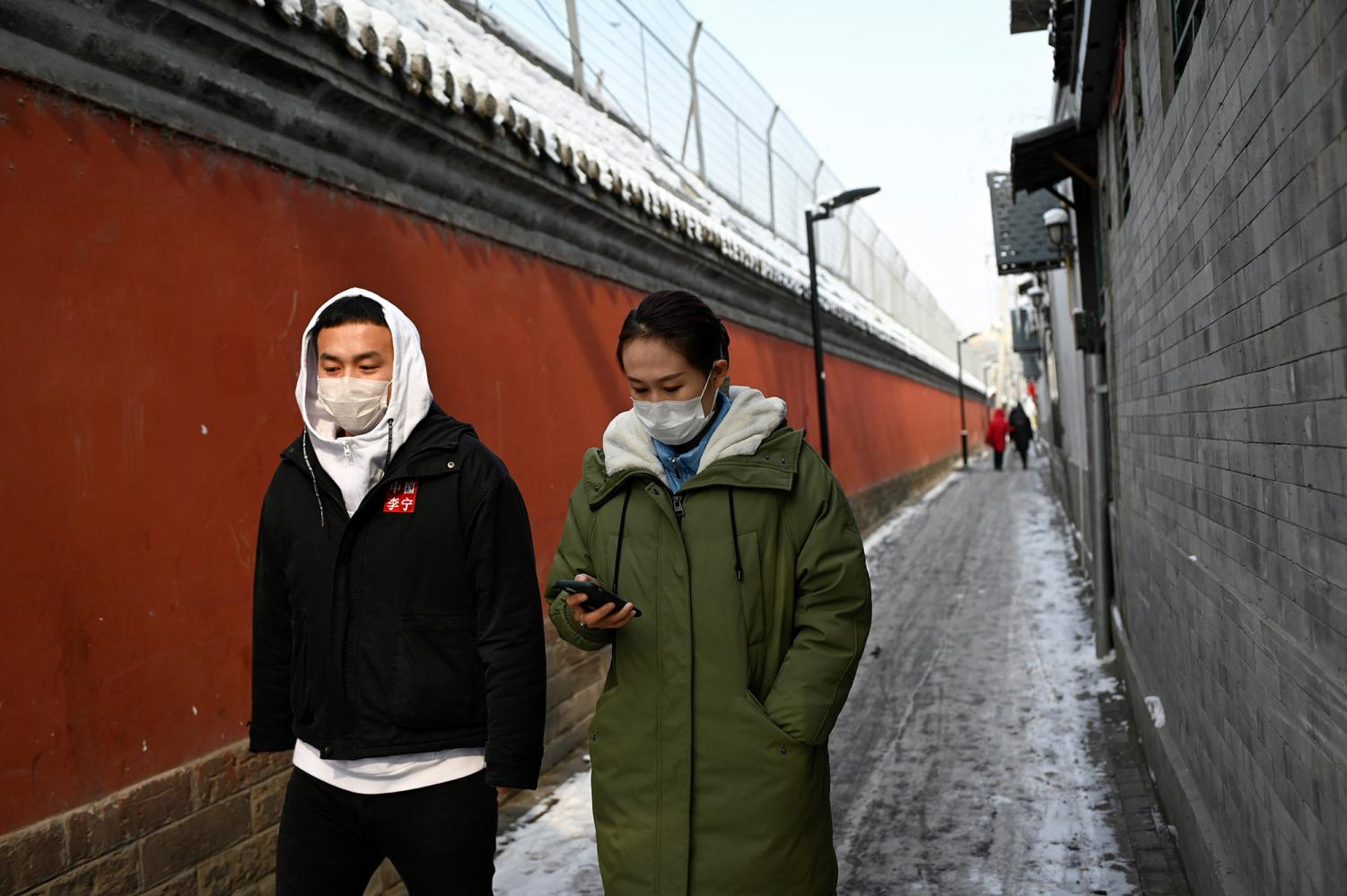 People wearing protective face masks walk through an alley in Beijing on Friday, Feb. 7, 2020. (AFP/Getty Images/TNS)