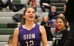 Junior Gabby Gaither flashes a smile to teammate sophomore Anna Sheedy as her name is called as a starter for the game against Blue Valley Southwest Feb. 5. Storm lost 67-55 to the Timberwolves.
