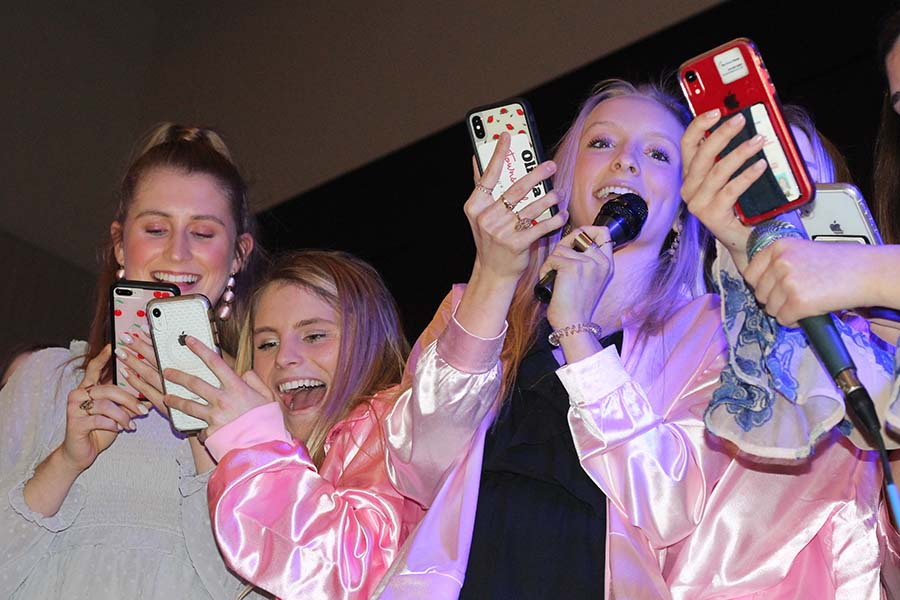Seniors Kyleigh Smith, Phoebe Fridkin and Olivia Townsend read lyrics off their phones and sing Take Me Home Country Roads by John Denver to their fathers during the annual Father-Daughter dance Feb. 9.