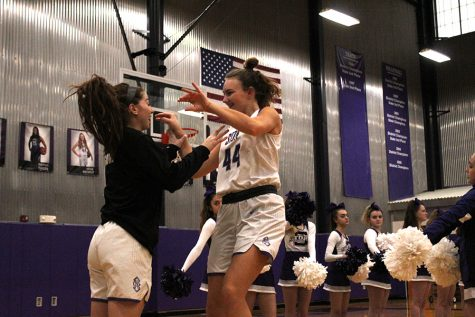 Juniors Gabby Gaither and Olivia Shively high five before the game. Varsity won 47-13 against Metro Academy Feb. 12.