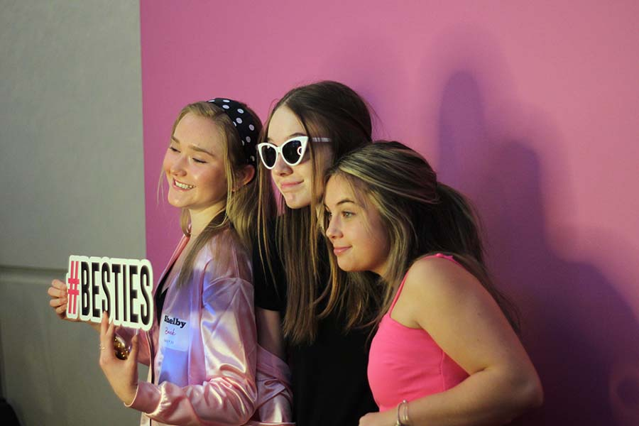 Freshmen Shelby Beck, Gabel Whittaker and Katie Kasper pose with props for the photo booth during the annual Father-Daughter dance Feb. 9. This years theme was Pink Ladies.