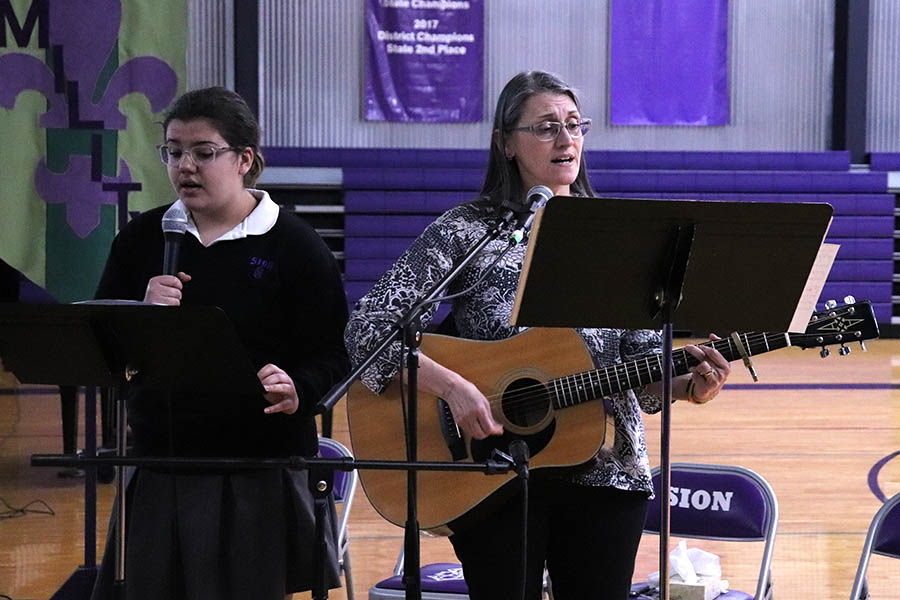 Senior+Maya+Bair+and+religion+teacher+Stephanie+Pino-Dressman+leads+the+school+in+song+during+the+annual+reconciliation+service+March+12.