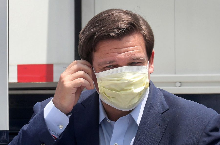Florida Gov. Ron DeSantis removes his face mask as he prepares for a news conference on April 8, 2020 at the Miami Beach Convention Center, which is being converted into an alternate care facility.