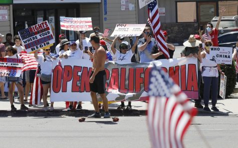 A skateboarder films protesters along Mission Blvd. in Pacific Beach during A Day of Liberty rally on Sunday, April 26, 2020. The protesters were against the government shutdown due to the coronavirus.
