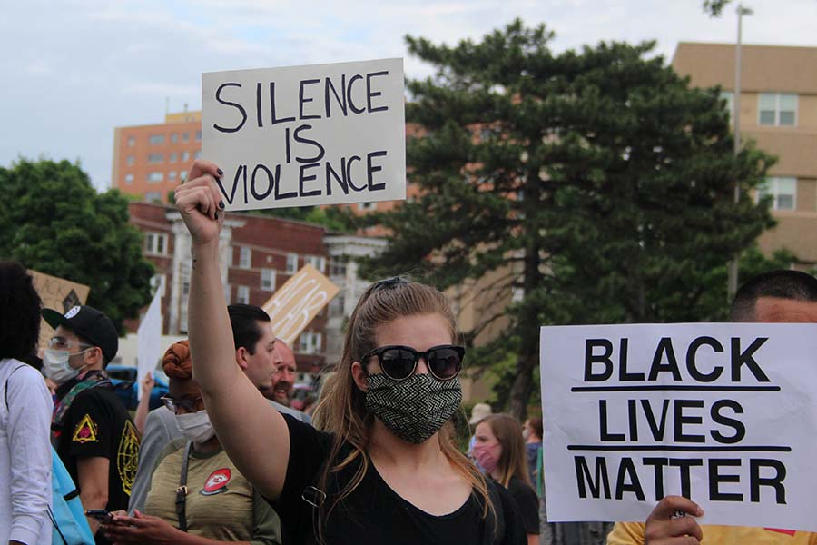 A protester wearing a mask holds up a sign reading