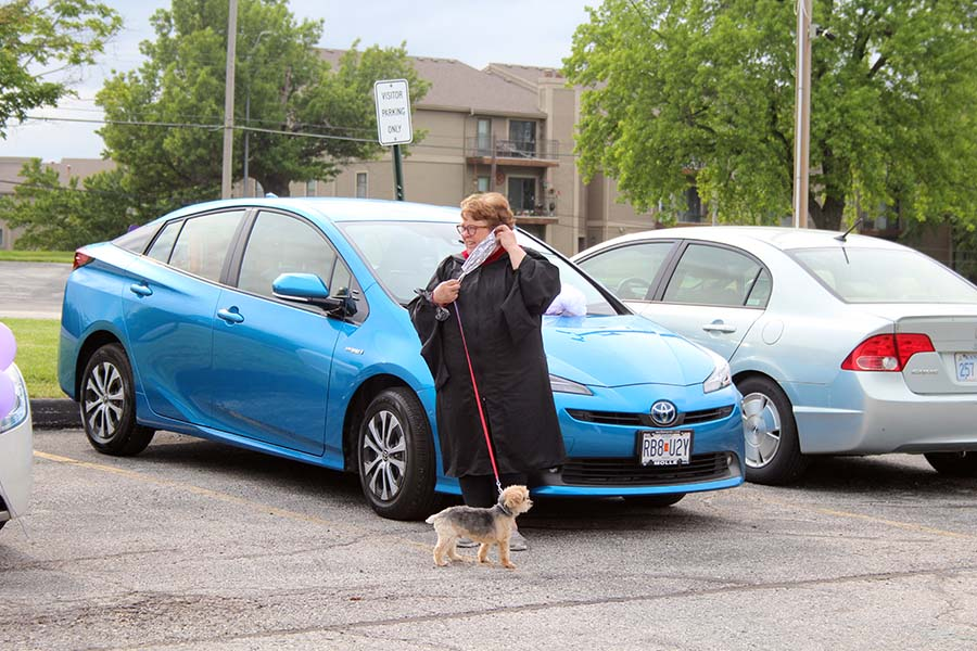 Theology teacher Bonnie Haghirian watches the graduation parade with her dog Tucker in the parking lot on May 21. Teachers gathered in the parking lot celebrate the Class of 2020 and to wish the seniors farewell.