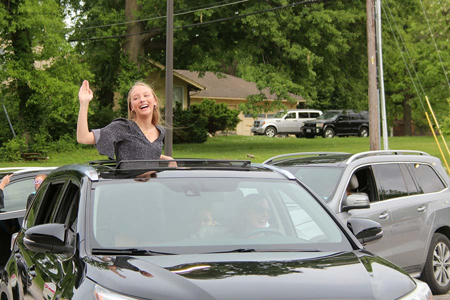 Senior Brie Bowes waves to her teachers during the graduation parade in the parking lot on May 21.