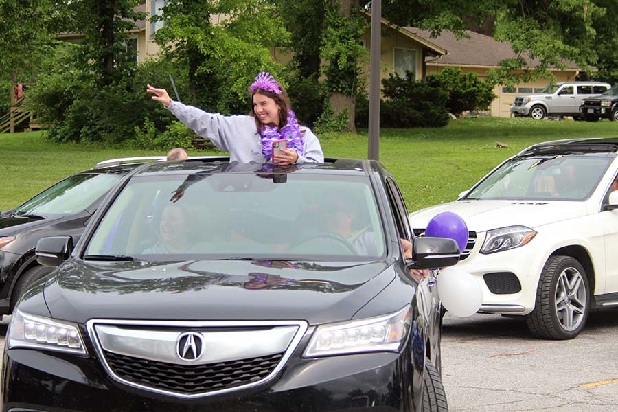 Senior Sophia Angrisano waves and greets her teachers from her car during the graduation parade in the parking lot on May 21.