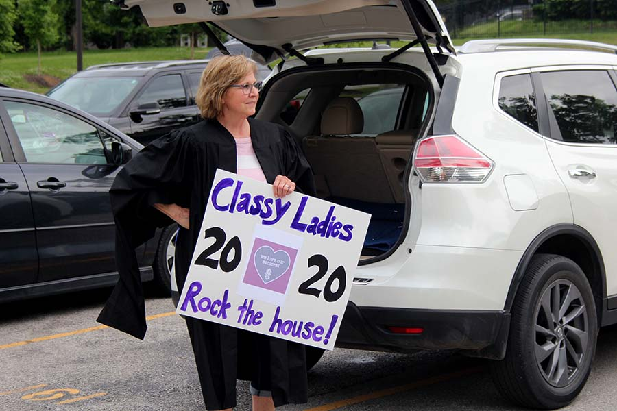 Assistant Principal for Student Life Fran Koehler watches the graduation parade and holds a sign in the parking lot on May 21.