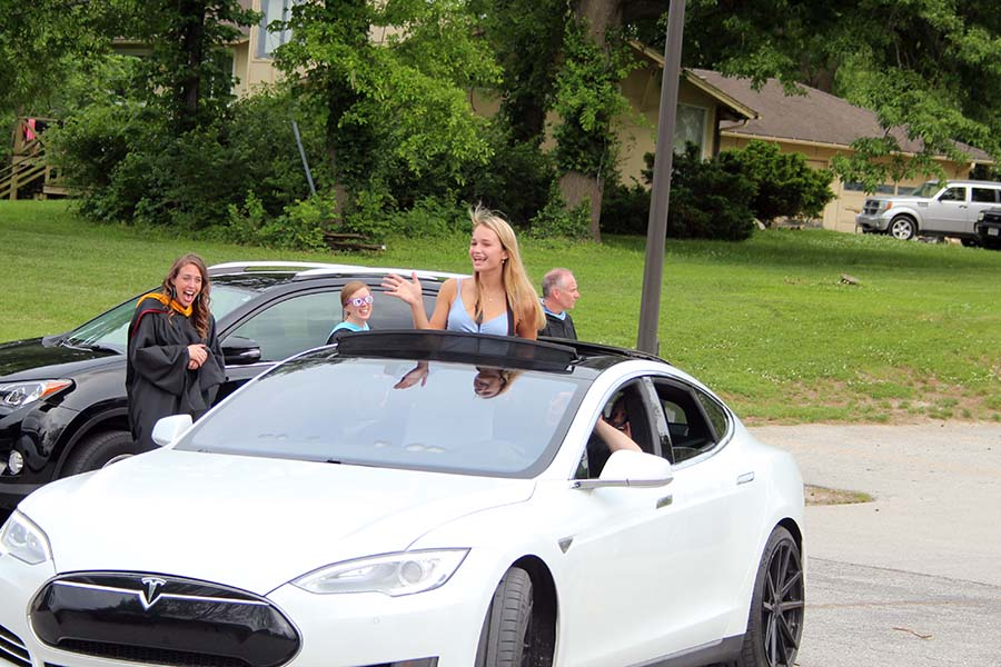 Senior Nina Trouvé waves to her teachers from her car during the graduation parade in the parking lot on May 21.