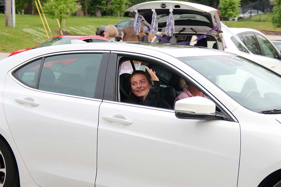 Senior Rose Orrick waves to her teachers during the graduation parade in the parking lot on May 21.