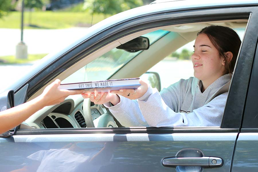 Sophia Angrisano, Class of '20 receives her copy of the yearbook from her car in the parking lot on Aug. 5. The theme of the yearbook is