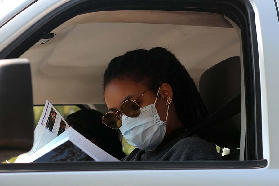 Munachi Okuagu, Class of '20 flips through her yearbook in her car after receiving her copy of the book in the parking lot on Aug. 5.