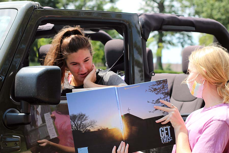 Reilly Jackoboice and Lily Henkle, Class of '20 laugh at a picture of Jackoboice in the yearbook in the parking lot on Aug. 5.
