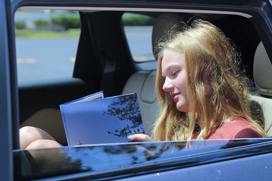 Libby Slaymaker, Class of 20 flips through her yearbook from her car after receiving it in the parking lot on Aug. 5.
