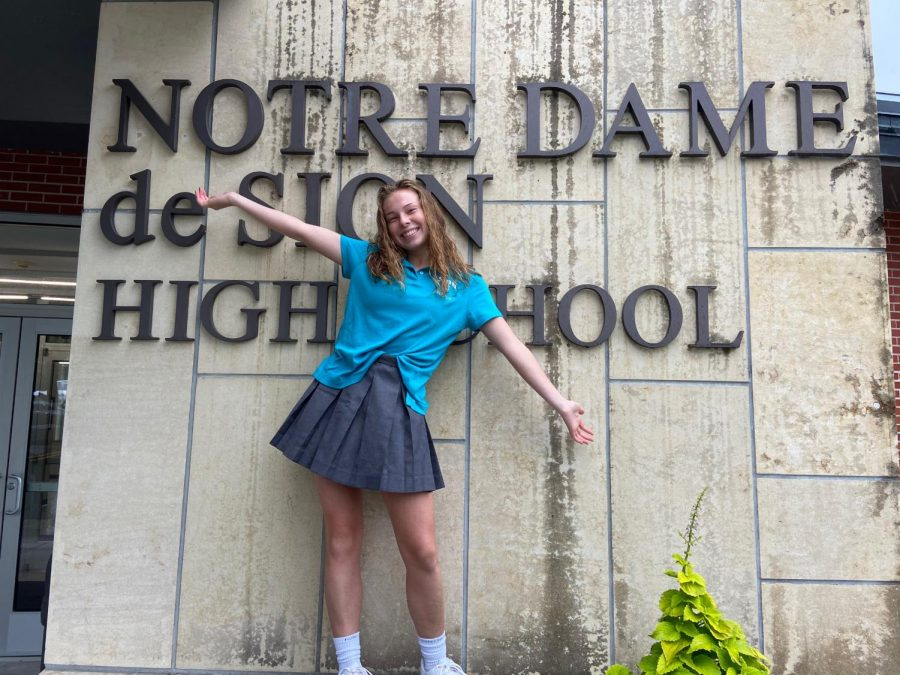 Senior Betty Christianson celebrates her first week at a new school in front of the main entrance. Christianson, who transferred from St. Teresa's Academy, made the decision to transfer in the summer.