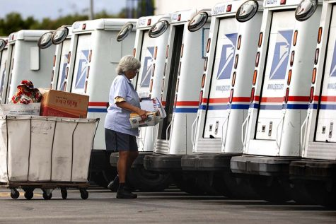 A mail carrier loads a truck for delivery at a United States post office in Torrance, California, on August 26, 2020. (Christina House/Los Angeles Times/TNS)