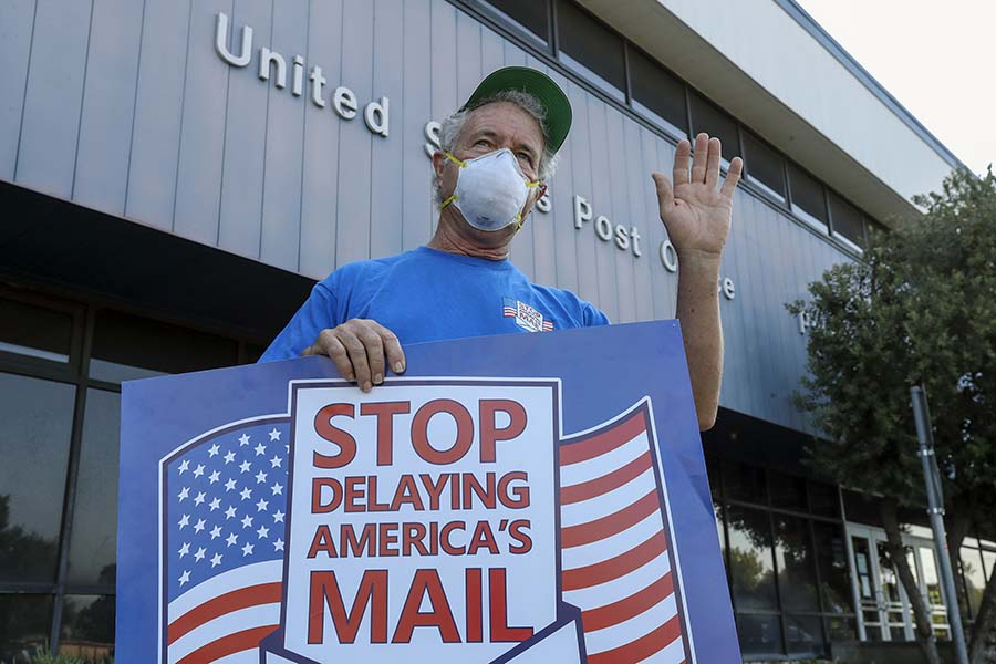 Paul Shevlin, a USPS employee, demonstrates in Pasadena, California, against Postmaster General Louis DeJoy's service changes within the U.S. Postal Service before the November general election. (Irfan Khan/Los Angeles Times/TNS)