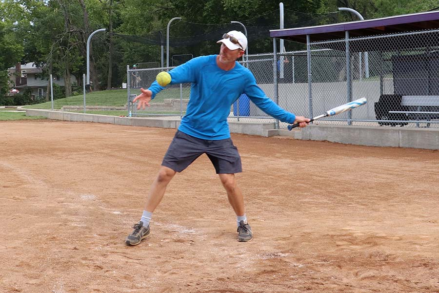 Softball coach Brett Lange swings at a ball during hitting practice with the softball team on Sept. 8. Lange is an avid softball supporter and hopes to improve the team's skills and mentality regarding the game.