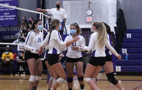 Seniors Shannon Karlin and Brynna Dow, sophomore Brynna Fitzgerald and junior Bridgette Conner huddle after a point during the volleyball game against St. Teresa's Academy in the gym on Sept. 8.