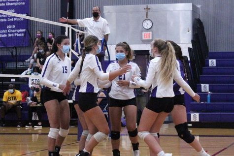 Seniors Shannon Karlin and Brynna Dow, sophomore Brynna Fitzgerald and junior Bridgette Conner huddle after a point during the volleyball game against St. Teresa