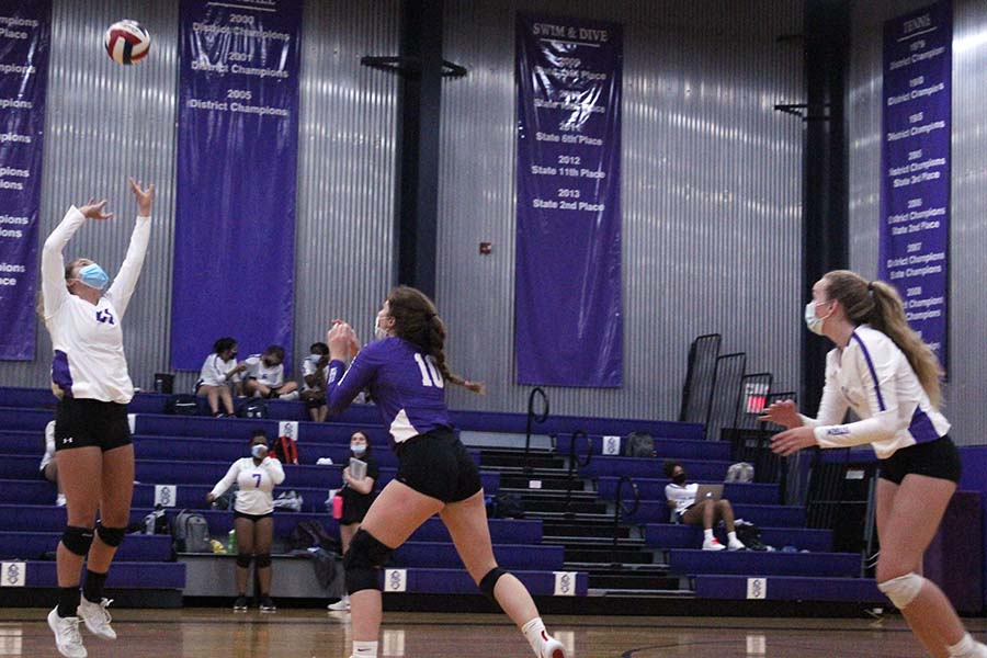 Sophomore Brynna Fitzgerald sets the ball up for senior Gabby Gaither while junior Bridgette Conner runs to place during the varsity volleyball game against St. Teresas Academy in the gym on Sept. 8. Players wore masks at all times during the match.