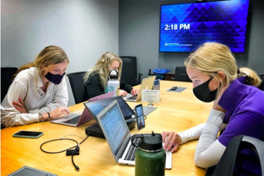 Seniors Mady Jenkins, Hannah McGraw and Violet Tumlin work on their projects for the Designing Real World Impacts class at the Burns & McDonnell headquarters on Sept. 2.